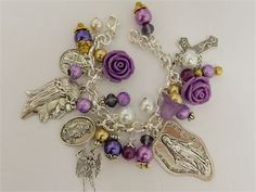 Miraculous Virgin Mary Jesus Christ handmade religious Catholic holy medal beaded charm bracelet.  Handmade lavender and purpled beaded charms dangle from a silver plated chain link bracelet surrounded by St Martha, St Benedict, Archangel Michael, Miraculous Virgin and Jesus Christ pewter and religious medals.  The head of Jesus Christ charm measures about 1 1/3 and the Blessed Mother medal is around 1 1/2  Acrylic rose and tulip shaped beads, white and gold glass pearls along with ...