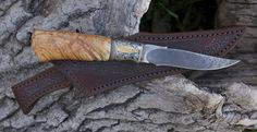 This fully carved trout knife has a stainless damascus blade, stainless and bronze fittings, and a stabilized box elder burl handle. Ray Cover engraved the guard with scrolls and flies. Sheath by NB Designs.