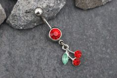 This dainty silver cherry dangle belly button ring features a high luster crystal cut gem with a captivating cherry dangle charm. Sparkle your way into style this summer with this super cute belly but