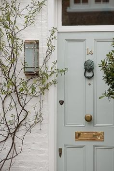 Pale blue front door color with white brick exterior