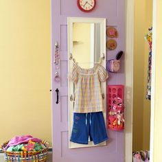 DIY Kids' Dressing Station: attach a full-length mirror to the closet door then stick on removeable hooks (2 to make a clothesline/clothespins for a shirt, and 2 beneath for the bottoms). Use additional adhesive-backed hooks for hair ties and necklaces and accessories. Recycle tea tins as holders for brush & comb, a grocery-bag holder for socks, cork coasters as tiny bulletin boards, etc.
