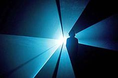 a photo of a person caught in the blue rays of a light installation