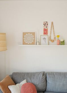 Displaying prints and little pieces on a narrow picture shelf.