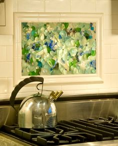 Create a beach mosaic (with seaglass, shells, pebbles....) in your kitchen! See examples here: http://www.completely-coastal.com/2015/11/kitchen-backsplash-ideas-beach-murals-nautical-ocean-blue-tiles.html