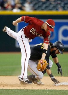 Arizona Diamondbacks' Aaron Hill, left, jumps over Pittsburgh Pirates' Sean Rodriguez (3) after a force-out at second base during the ninth inning of a baseball game Sunday, April 26, 2015, in Phoenix. The Pirates defeated the Diamondbacks 8-0. (AP Photo/Ross D. Franklin)