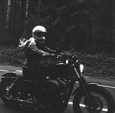 Morgan Gilman Garritson riding a black Sporty at twilight with flowing blonde hair. Photograph by Lanakila MacNaughton of the Women's Moto Exhibit (website).