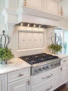 Light gray and silver accents and a white tile backsplash add dimension to this traditional white kitchen. The pro-style gas cooktop is perfect for the master chef in the house. Marble countertops complete the polished, sophisticated look.