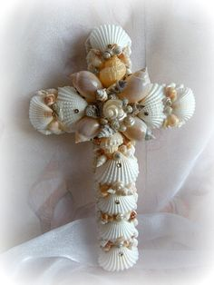 A beautiful cross perfect wall accessory for the beachy bungalow. Measures 9 1/2 x 6 inches. I used White arca shells covers the body, the