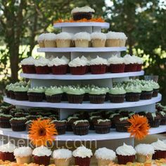 A multi-tiered display held four kinds of cupcakes, including chocolate, coconut cream, and red velvet. Fresh orange flowers and petals made the setup fit the wedding palette.