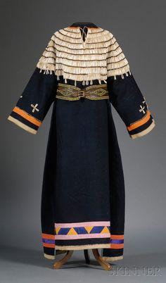 AMERICAN INDIAN & ETHNOGRAPHIC ART - SALE 2506 - LOT 322 - PLAINS BLUE TRADE CLOTH WOMANS DRESS, LAKOTA, C. LATE 19TH CENTURY, THE MUSLIN-BACKED YOKE WITH ROWS OF DENTALIA SHELLS AND BUGLE B... - Skinner Inc
