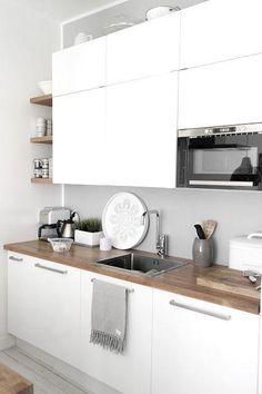 Cocina con muebles blancos y encimera de madera