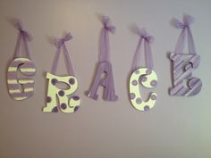 Hand painted wooden letters with bows. I painted these for my step daughters bedroom. Then hot glued bows from them to hang them up.