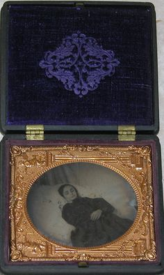 Sixth-plate tintype of post-mortem of a young girl. Image shows subject on bed, from knees–up wearing dark dress. ~✿•❤•✿~