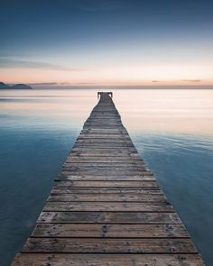 """Der Sonne entgegen – meterweit ragt der alte Holzsteg in das Mittelmeer in der Bucht von Alcudia auf Mallorca.  (Vliestapete """"Morning Breeze"""", SH021-VD2)"""