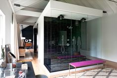 Mark Zeff's Hamptons House: Glass walls showcase the dramatic black-and-white shower in the master suite, which is punctuated by a vibrant bench.