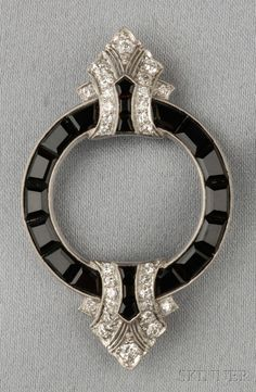 Art Deco Platinum, Onyx, and Diamond Brooch, set with fancy-cut black onyx, old European-cut diamond accents, millegrain details, no. 3044, lg. 2 in., maker's mark.