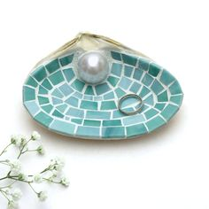 How pretty is this large sea shell ring holder dish done in sea green stained glass mosaic tiles?! Perfect for holding wedding rings or other small jewelry, even coins, it looks so lovely on the night stand. It also can be used as an alternative ring bearer pillow at a beach wedding. Created using an actual sea shell found on the beach in South Boston, all of the stained glass tiles are cut by hand. A large pearl bead provides the perfect accent. Comes wrapped in brown craft paper, tied…