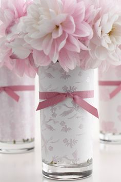 DIY: Paper Wrapped Tumblers--old glass tumblers wrapped in wedding invitation paper, tied with a little grosgrain ribbon and filled with pretty blooms