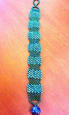 *Two sizes of peacock colored seed beads are peyote stitched in an alternating pattern    *Bead clasp is color changing - reacts to temperature and