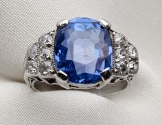 Circa 1930. This fantastic 18KT white gold Deco ring is centered by a beautiful 6.37 carat oval cut sapphire. The shoulders of this magnificent ring have a stair step pattern sparkling with ten Old European cut diamonds with a .50 carat total diamond weight, SI2-I1 clarity and I-J color. The vintage Art Deco ring measures 11.30mm wide and 6.50mm tall at the top, tapering to 2.30mm wide and .40mm thick at the bottom of the shank.