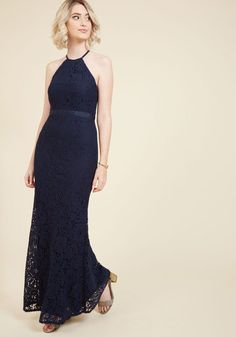 As you peek around the tall front door in this navy blue gown, you just know its high neckline and crisscrossing back straps will look and feel oh-so-fittingly splendid in the estate. Overlain with sumptuous floral lace, this maxi reflects the luxury of rich paneling and stained glass windows that serve as your backdrop. Lovely!