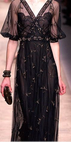 Valentino pays homage to the 1910s silhouette of evening dresses especially with these flared sleeves not unlike early interpretations of the kimono sleeves and low v-shaped neckline. From the waist, the skirt flairs out slightly, allowing a sort of trumpet/flower shape.