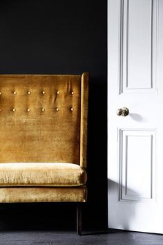 Mustard sofa with high back contrasts with dark paintwork in Living Room Design Ideas. Take a look on HOUSE - design, food and travel by House & Garden.