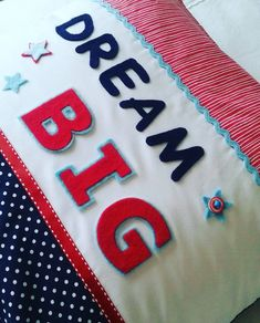"""A stunning focal point in your little ones nursery or bedroom, this beautiful ben style """"Dream Big"""" cushion features luxury designer fabric with varsity lettering, stars & buttons that makes this extra special and adds a really finishing touch to any room. Big Cushions, Star Buttons, Luxury Designer, Dream Big, Little Ones, Fabric Design, Nursery, Kids Rugs, Touch"""