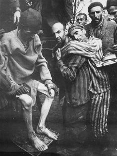 """The evacuation of survivors from the Woebbelin concentration camp to an American field hospital. Among those pictured, center, carrying a fellow survivor is Aliende, a political prisoner. WW2 May 4, 1945 The original caption reads """"This is one of a series of pictures taken at German Concentration Camp in Woebling, Germany after its capture by troops of the 82nd Airborn Division, 9th Army. These former prisoners of the Germans are being taken to a hospital for much needed medical attention…"""
