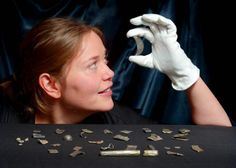 Archaeologist examines a crescent shaped brooch fragment from the Aberdeenshire hoard. Image credit: © Phil Wilkinson / University of Aberdeen.
