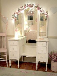 If this makeup vanity was its original color (stained) it would be just like my great grandma's vanity!  LOVE the lights behind & on this flower garland above the mirror.