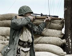 A U.S. Marine Marksman using a telescopic sight and with his Springfield cocked and ready, waits for a troublesome North Korean sniper to pop up so he can pick him off in Seoul, capital city of South Korea on Sept. 28, 1950