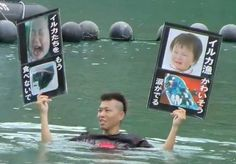 A young Japanese activist protests the Taiji dolphin drives in the cove. On the other side of the ne...