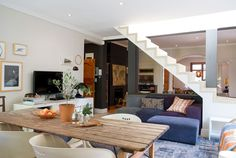 The open-plan kitchen connects with the living area. The sofa here was designed by Liesel and custom made by Patrick's Upholstery .