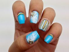 Uñas azules con cadenas, plumas y brillantitos.