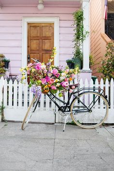 Little white picket fence, adorable pink cottage and a beach cruiser with a basket of blooms.