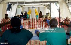 News Photo : A health worker wearing a protective suit assists...