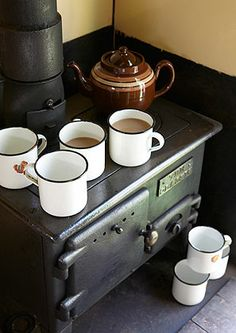 Enamelled Tin Mugs, black lead stove and brown betty teapot