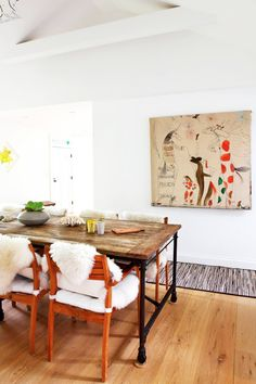 Salvaged wood dining table with white chairs and artwork