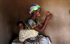 A woman prays with her child during a Sunday service in a village near Bujumbura, Burundi, May 31, 2015. REUTERS/Goran Tomasevic