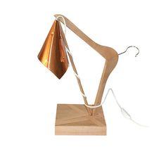 Sorretto da una gruccia in legno, il paralume, di forma conica, è realizzato con un foglio in rame modellabile opportunamente richiuso da fermacampioni color oro. La base in legno multistrato è rifinita con bordatura flessibile in legno color naturale. Ideale per dare un tocco di eleganza