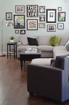 above the couch family photos.  various   colored frames would be nice on a neutral wall.  family room wall by croskelley, via Flickr