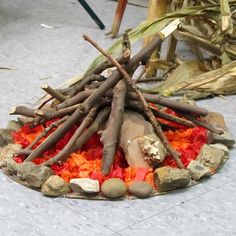 """""""Fire"""" -- Staple gun orange and red construction paper to large cardboard cutout. Add """"rocks"""" and sticks around."""