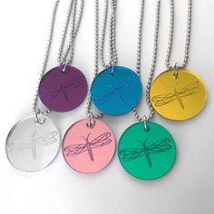 *This listing is for one (1) mirrored acrylic dragonfly necklace.*   Each one of these stunning dragonflies is carefully etched into the back of 1/8 inch thick piece of mirrored acrylic. Mirrored acrylic has the same beautiful, reflective surface of a glass mirror, but is completely shatter-proof. Available in blue, pink, purple, yellow, green and silver. Just choose your color choice from the drop down menu before checkout.  The pendant measures 1 1/4 (33mm) round and is strung on...