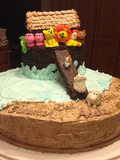 Noah's ark cake. Fondant animals sitting atop a chocolate layer cake iced in dark chocolate buttercream icing. Hut made from rice crispy treats and iced same. Plank is rice crispy treat  dipped in chocolate. Cake base is half chocolate half vanilla with a chocolate chip cream center and iced in butter cream.