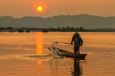 Along the Mekong River, Thailand - We arrived at the river at first light and made our way down to the rivers edge with headlamps lighting or way.  Fishermen were already there getting their boats ready for the day.  Here, a fisherman paddles in the light of sunrise.