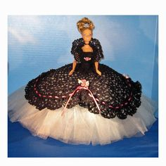 This is a stunningly dressed Barbie in a cotillion ball gown of black crochet and whisper grey tulle.     Included are the Barbie doll, the gown, shawl collar, crocheted shoes, crocheted panties, black choker rhinestone necklace, rhinestone earrings, rhinestone tiara and the stand.    There are 5...