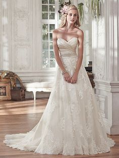Maggie Sottero - KAMIYA, Timeless and elegant, this romantic lace and tulle A-line wedding dress features a stunning L'Amour satin pleated bodice and lightweight lace and tulle skirt, accented with a delicate Swarovski crystal embellishment at the waist. Finished with half corset and half zipper closure.