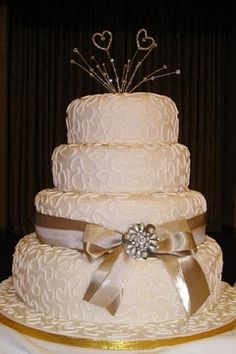 Elegant three tier wedding cake decorated with ivory swirls and champagne coloured satin bow and ribbon. Garnish with an elegant pearl brooch. From Caramilis www.flickr.com    ........   #wedding #cake #birthday