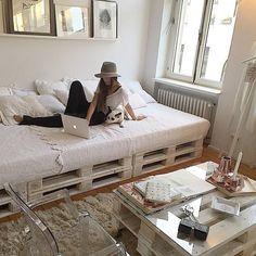 Estrados de paletes sobrepostos, revestimento patinado provençal e um confortável colchão se transformam em um belo sofá-cama. A mesa de centro, também de palete, é feita com ripas vazadas, mas ganhou uma proteção extra de vidro no tampo, para tornar o apoio de objetos mais confortável. Aqui a decoração é clean, totalmente branca. Observe que o colchão foi coberto com uma bela colcha; e travesseiro e almofadas fazem o papel de encosto. Tudo simples e econômico, mas chique!